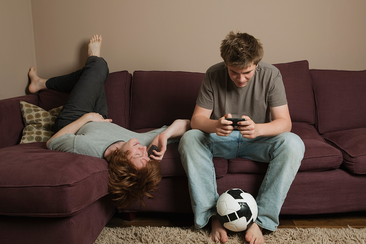 Teenagers using phone on couch