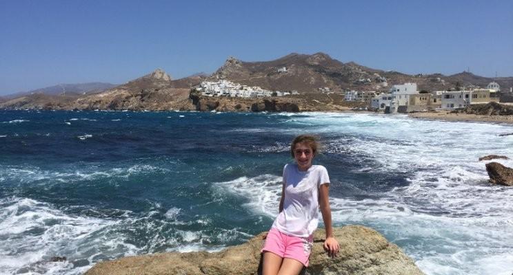 Teenage Girl Sitting on Rock in Front of Ocean